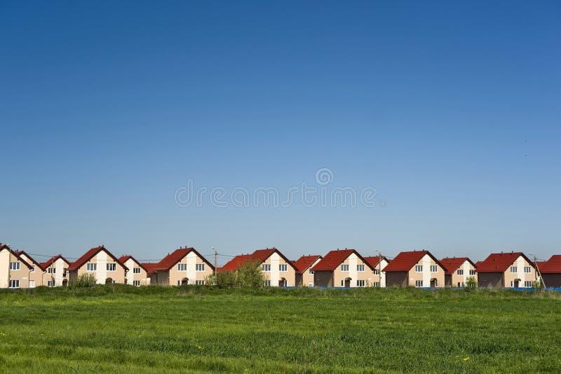 Nuovi cottage e cielo blu fotografia stock