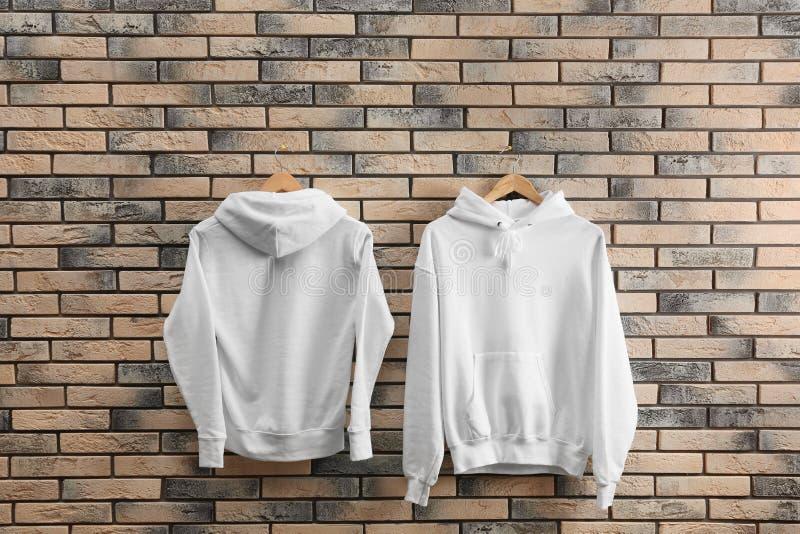 Nuovi maglioni di maglia con cappuccio con i ganci sul muro di mattoni fotografia stock