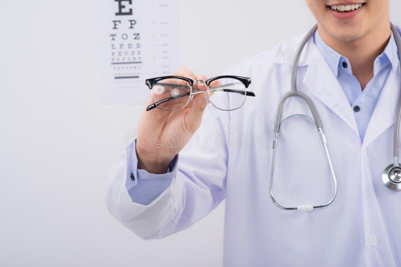Nuovi vetri Optometrista che dà gli occhiali per provare immagine stock