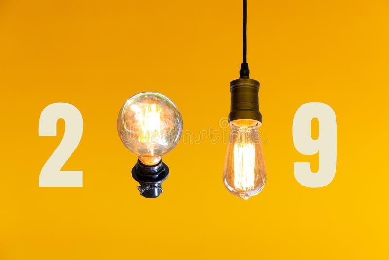 Nuovo anno 2019 con la lampadina d'annata su fondo arancio fotografia stock