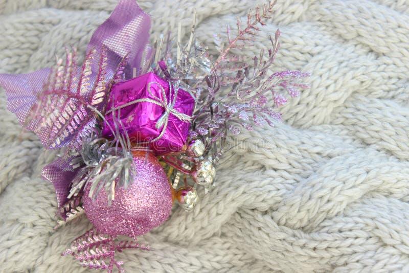 Nuovo anno del fondo, Natale Decorazione di Natale, ramo porpora con le palle e regalo isolato sul backgrou tricottato strutturat fotografie stock libere da diritti