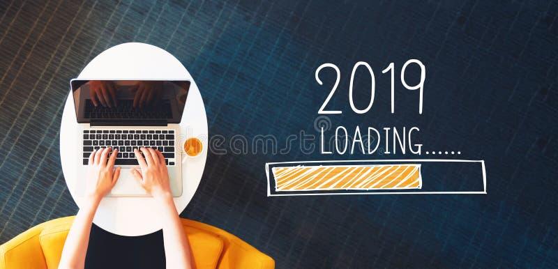 Nuovo anno di carico 2019 con la persona che per mezzo di un computer portatile fotografia stock libera da diritti