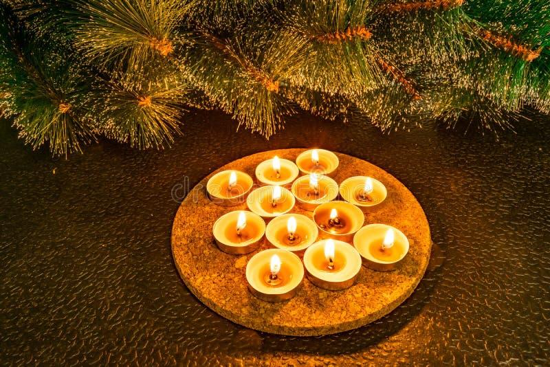 Nuovo anno e Natale, pino artificiale verde su un fondo nero alla luce delle candele della cera Tocchi familiari caldi gialli, io fotografia stock libera da diritti