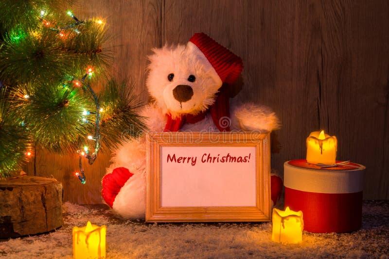 Nuovo anno, orso di Natale che si siede sotto un albero di abete con una struttura di legno con il Buon Natale dell'iscrizione! fotografia stock
