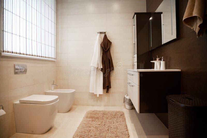 Nuovo bagno luminoso interno con la passeggiata di vetro nei bordi della doccia, gabinetto marrone di vanità ed accoppiato con la fotografia stock