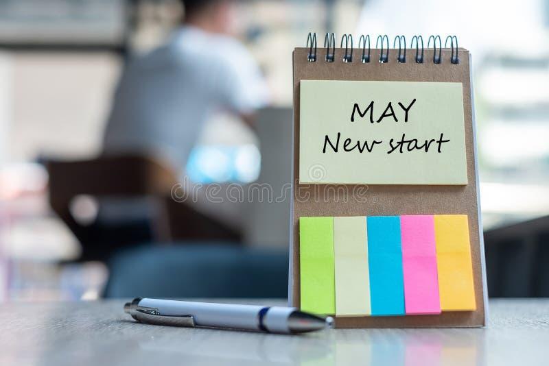 Nuovo inizio di maggio con il modello di ricordo della carta per appunti con la penna sulla tavola di legno copi lo spazio per il fotografia stock libera da diritti
