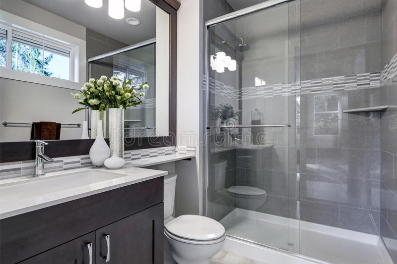 Nuovo interno luminoso del bagno con la passeggiata di vetro in doccia fotografie stock