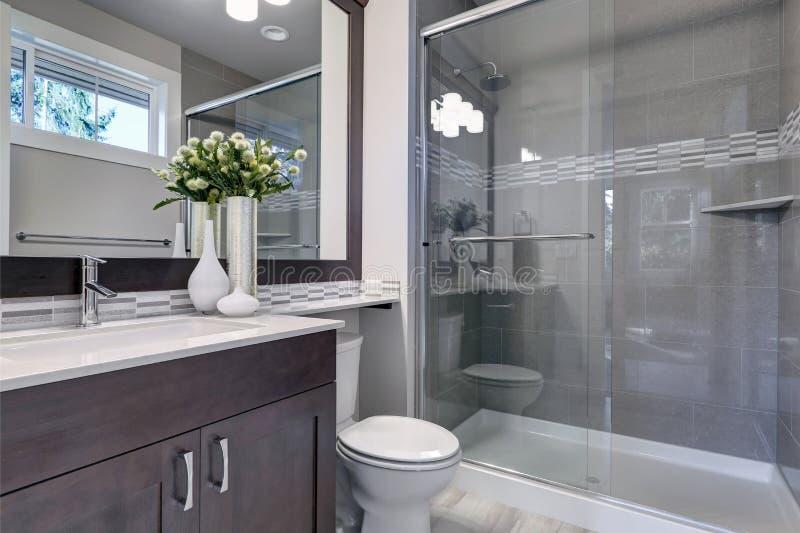 Nuovo interno luminoso del bagno con la passeggiata di vetro in doccia fotografia stock libera da diritti