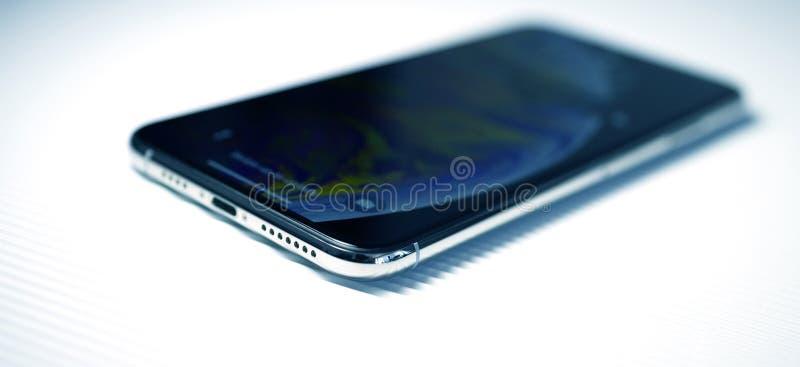 Nuovo iphone Xs contro l'argento dell'angolo del fondo della banda fotografia stock
