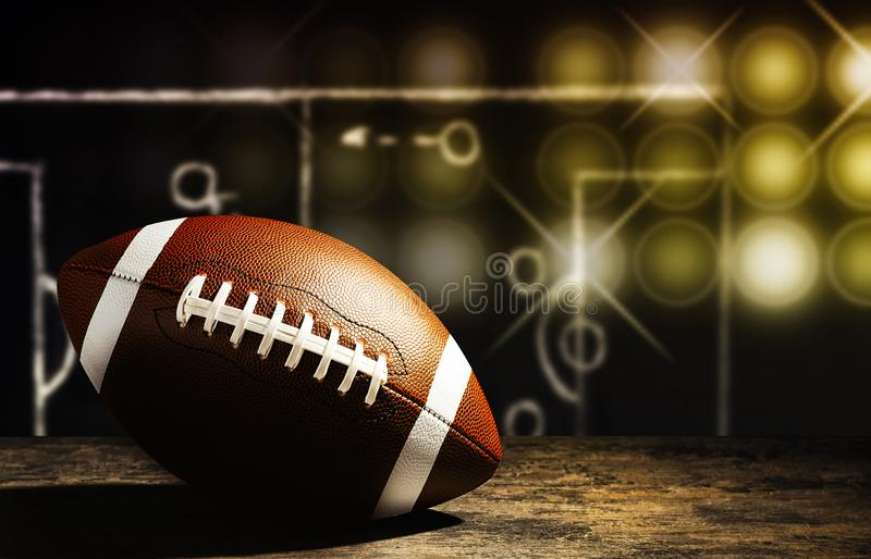 Nuovo pallone da calcio americano sulla tavola contro la lavagna con lo schema della partita di football americano fotografia stock libera da diritti