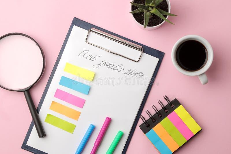 Nuovo scopo 2019 testo su carta con la lente degli autoadesivi di colore e una tazza di caffè su un fondo rosa luminoso fotografia stock