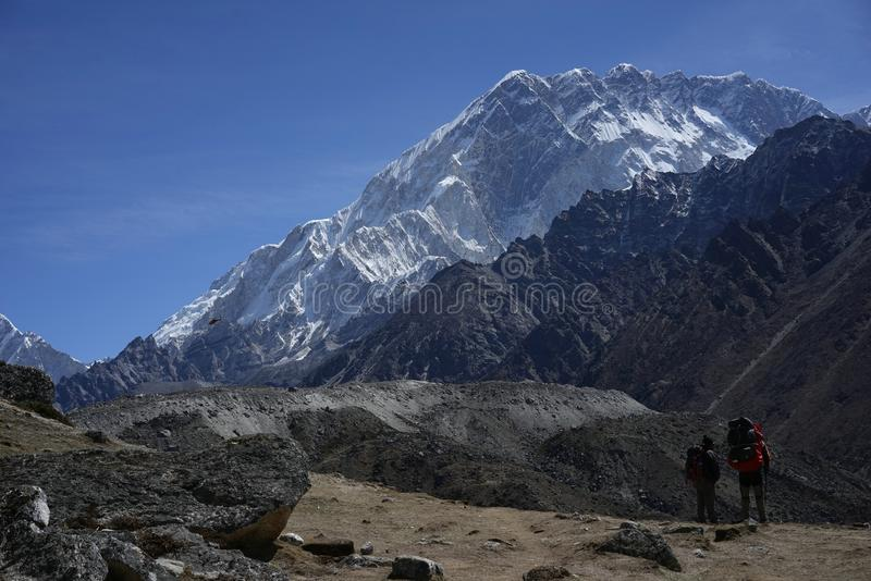Nuptse and trekers in Himalayas stock photo