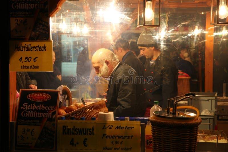 NUREMBERG, DUITSLAND - DECEMBER 22, 2013: De modieuze verkoper verkoopt worsten bij nacht bij de Kerstmismarkt, Nuremberg, Duitsl stock afbeelding