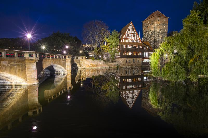 Nuremberg in Germany. The beautiful evening view over the Pegnitz river towards Weinstadel House, Hangmans Tower and the Max Brucke bridge, in Nuremberg, Germany stock photography