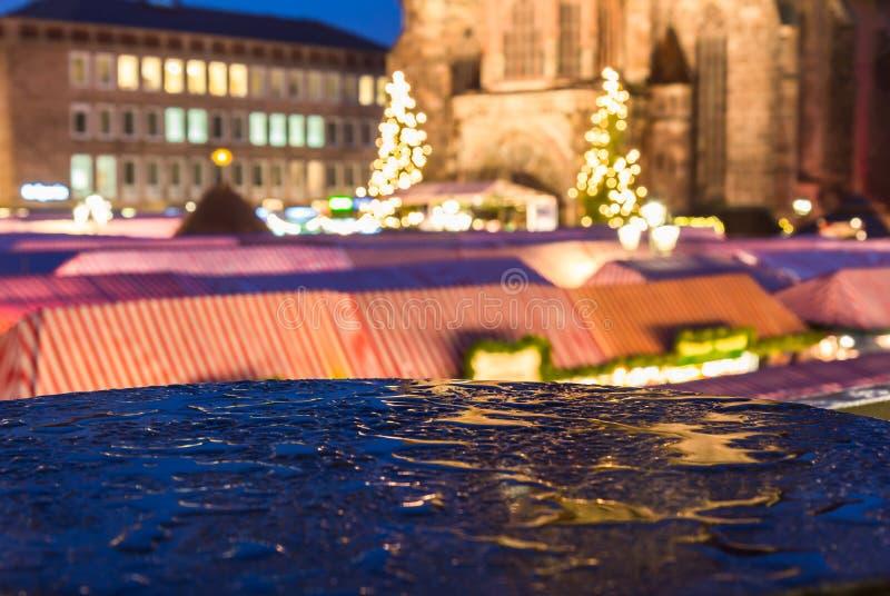 Nuremberg, Germany-Christmas Market in rain- blurred evening scenery. Nuremberg, Germany- beautiful evening scenery with blurred church, stalls and sharp drops royalty free stock image