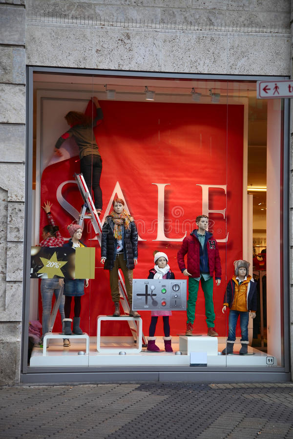 NUREMBERG, GERMANY - DECEMBER 23, 2013: Storefront with mannequins in the process of decoration for sale, Nuremberg, Germany stock image