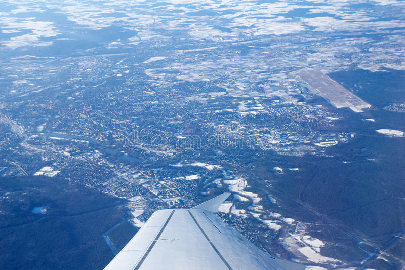 NUREMBERG, GERMANY - JAN 20th, 2017: View through aircraft window onto jet wing, wingview over snow covered city of royalty free stock photo