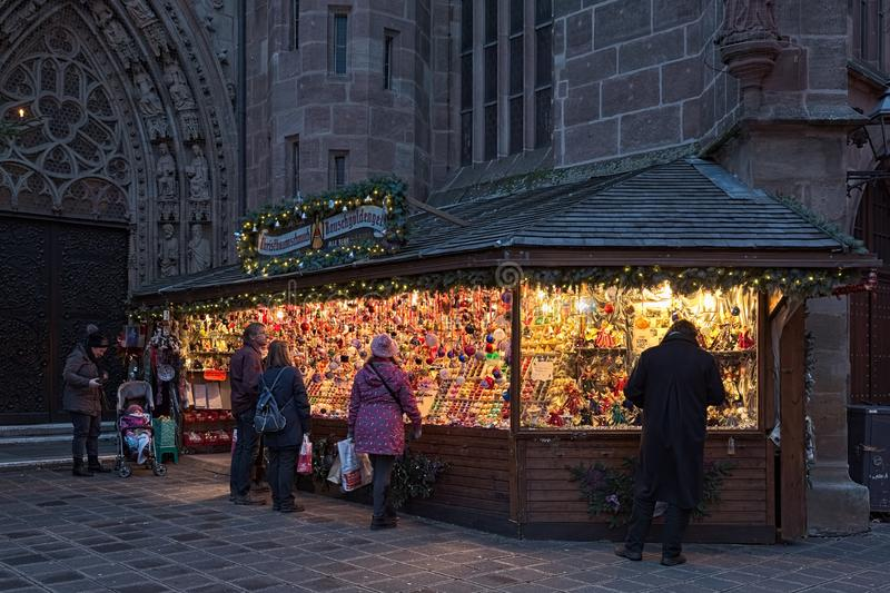 Market stall with Christmas decorations in Nuremberg, Germany. Nuremberg, Germany. Market stall with Christmas decorations at the entry to Frauenkirche in dusk royalty free stock photos