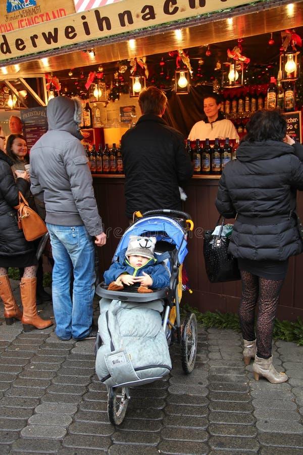 NUREMBERG TYSKLAND - DECEMBER 23, 2013: Ett barn i ett roligt hattsammanträde i en pram och väntande på föräldrar germany nurembe royaltyfri fotografi
