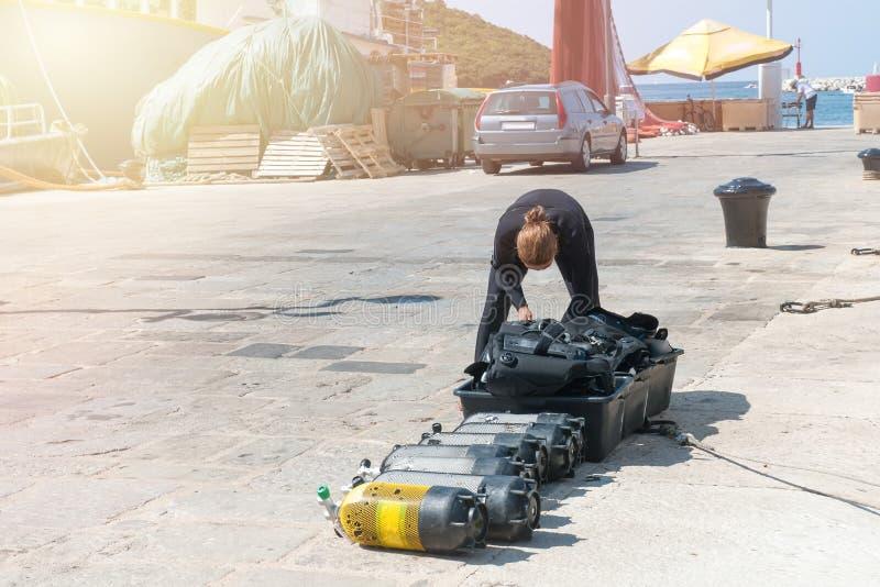 Nurków czeki wietrzą zbiorniki dla akwalungu pikowania na molu Pełni zbiorniki tlenu i nurkowy wyposażenie przygotowywający nurko obraz stock