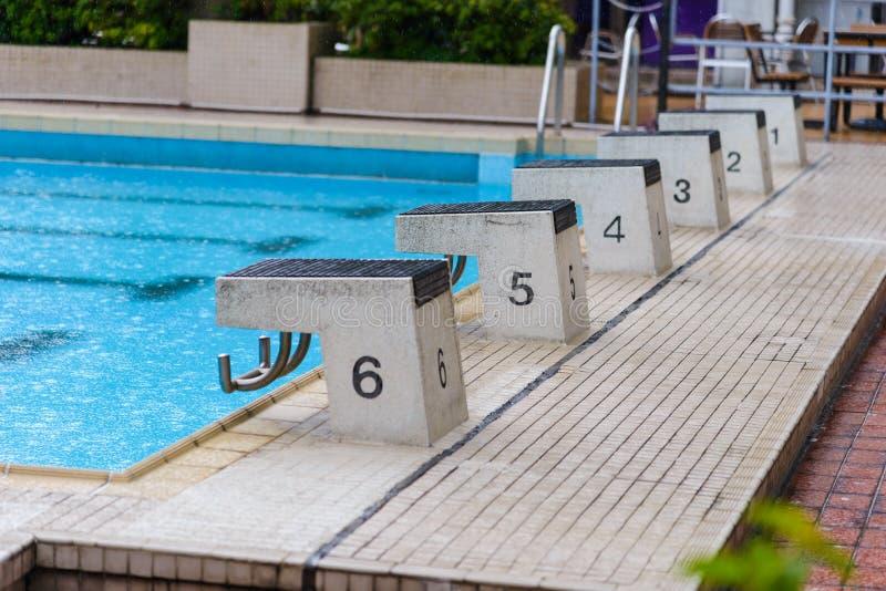 Nurkowi bloków stojaki z liczbami w plenerowym basenie na deszczowym dniu fotografia royalty free