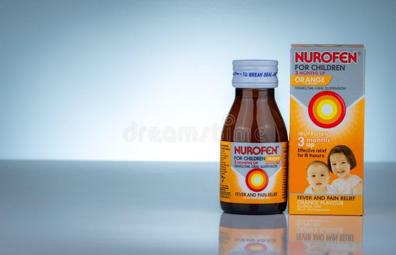 Nurofen en la botella ambarina en fondo de la pendiente Suspensión oral del ibuprofen para los niños Medicina para la fiebre y el fotos de archivo libres de regalías