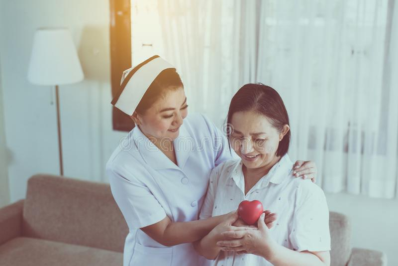 Nurse and Asian elderly woman holding heart red model on hands together,Senior healthy and taking care concept royalty free stock images
