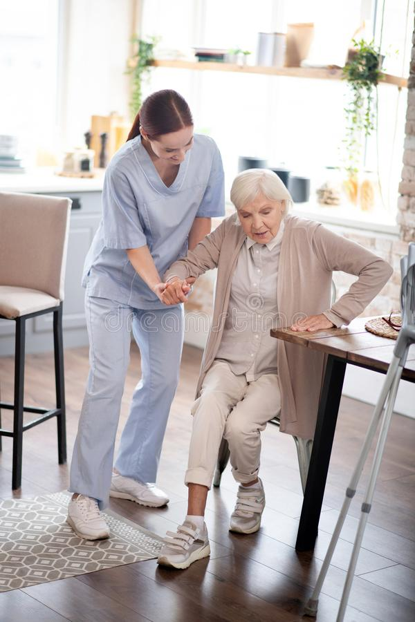 Nurse assisting aged woman in making steps after surgery royalty free stock photos