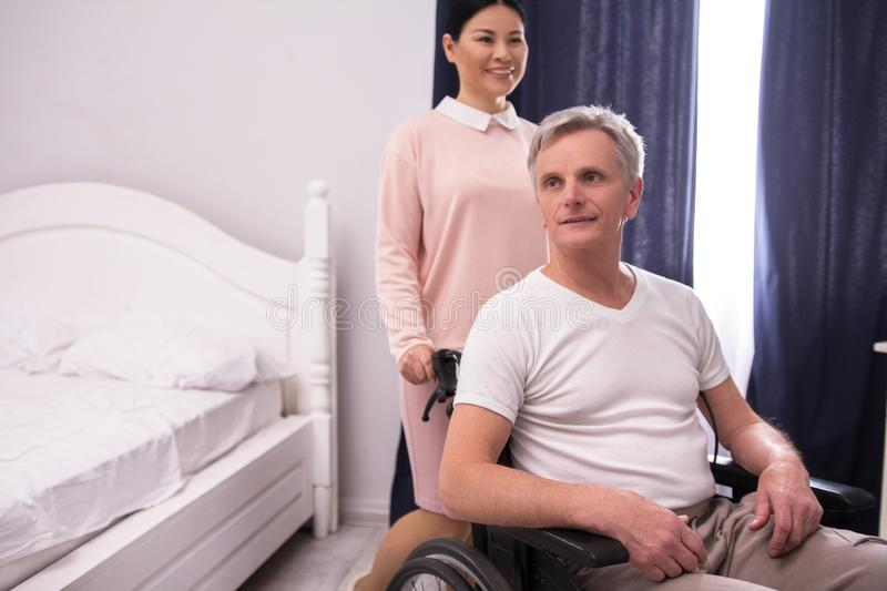Nurse assisting disabled man. stock photo