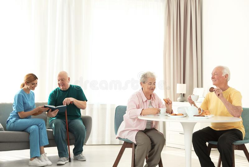 Nurse assisting elderly man while senior couple having breakfast royalty free stock image