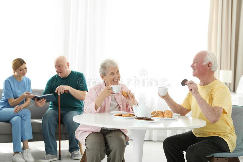 Nurse assisting elderly man while senior couple having breakfast stock image