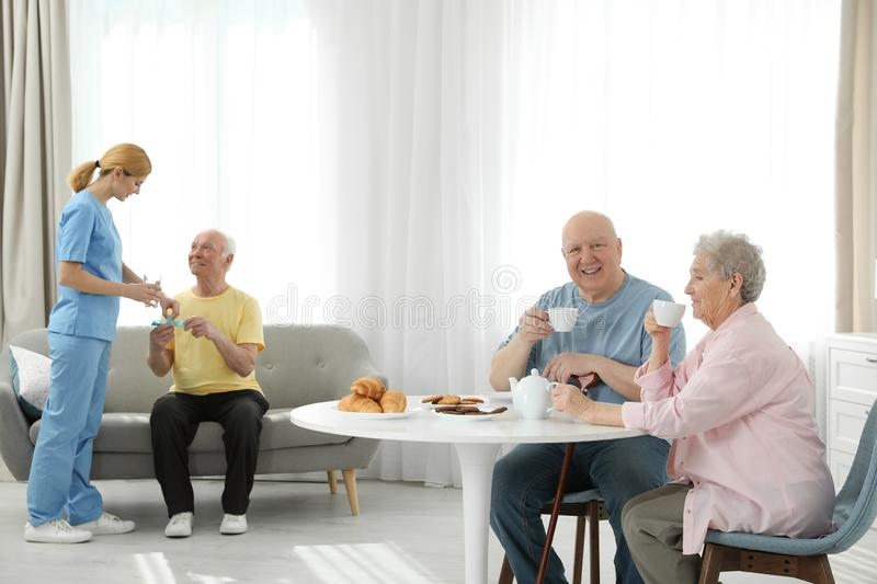 Nurse assisting elderly man while senior couple having breakfast royalty free stock images