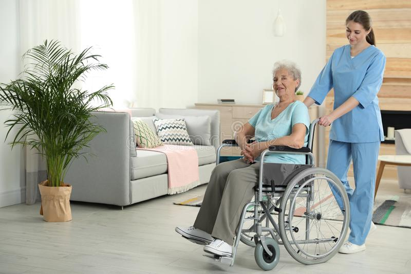 Nurse assisting elderly woman in wheelchair indoors stock photos