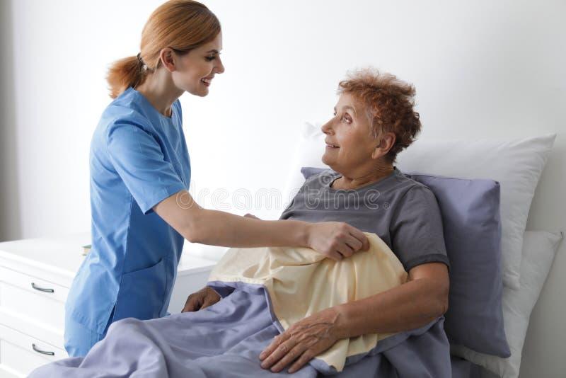 Nurse assisting elderly woman in bed. Nurse assisting elderly women in bed indoors stock images