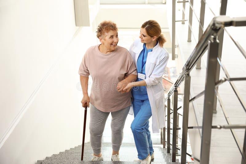Nurse assisting elderly woman on stairs. Nurse assisting elderly women on stairs indoors stock photos