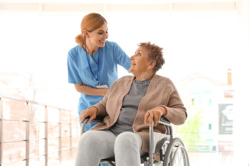 Nurse assisting elderly woman in wheelchair. Nurse assisting elderly women in wheelchair indoors stock photography