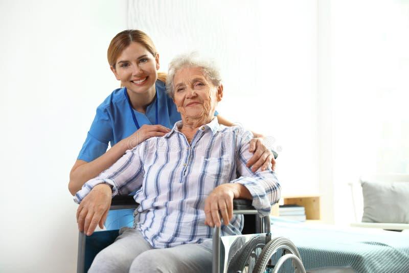 Nurse assisting elderly woman in wheelchair royalty free stock photo