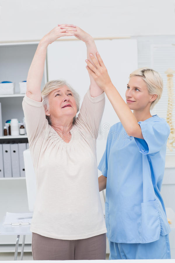 Nurse assisting female patient in raising arms. Nurse assisting senior female patient in raising arms at clinic royalty free stock photography