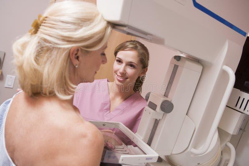 Nurse Assisting Patient Undergoing Mammogram royalty free stock photos