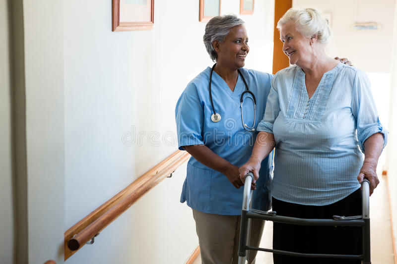 Nurse assisting patient in walking with walker at retirement home. Nurse assisting senior patient in walking with walker at retirement home royalty free stock photo