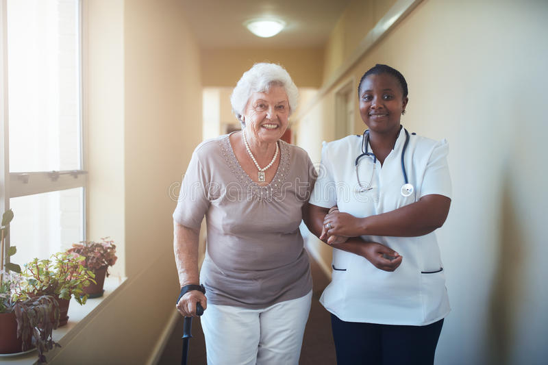 Nurse assisting a senior patient to walk royalty free stock photography
