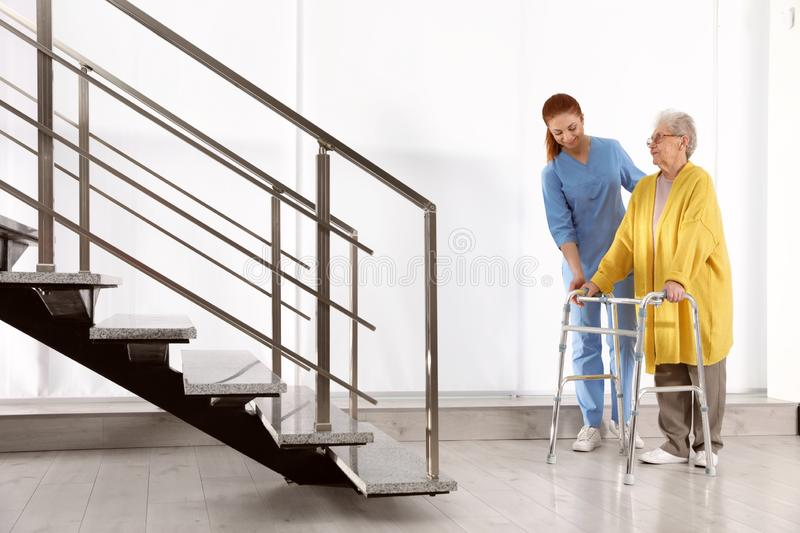 Nurse assisting senior woman with walker royalty free stock photo