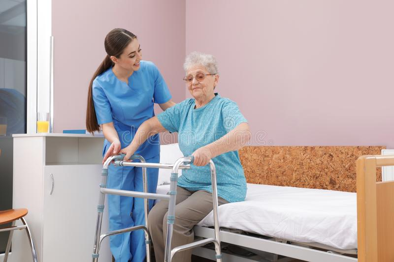 Nurse assisting senior woman with walker to get up from bed stock photo