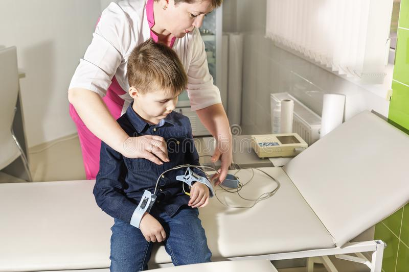 A nurse attaches electrodes to the boy to remove the cardiogram stock photography