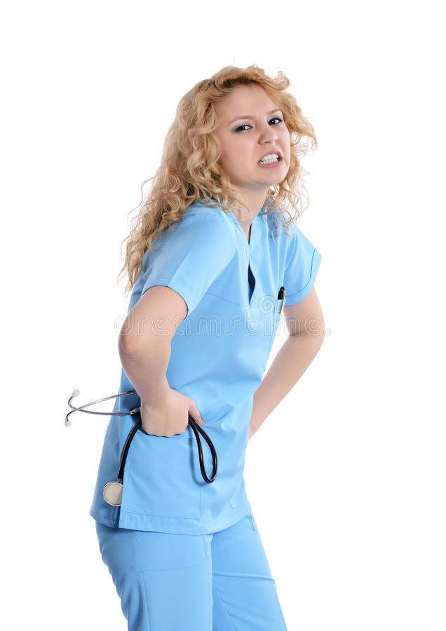 Nurse Back Pain. Woman bends over and flinches in pain in her back. healthcare concept stock photo
