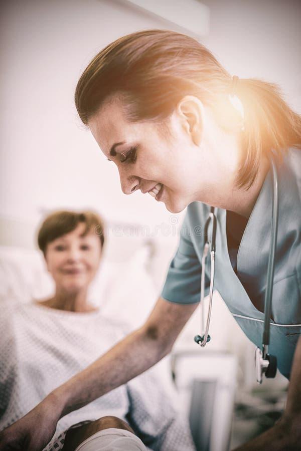 Nurse bandaging leg of patient. Smiling nurse bandaging leg of patient in hospital royalty free stock photography