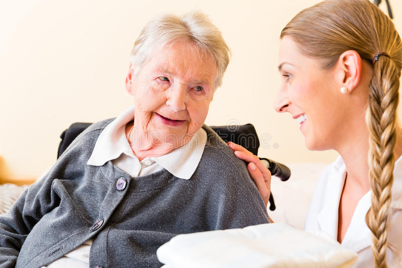 Nurse bringing supplies to woman in retirement home. Nurse bringing supplies to senior women in retirement home royalty free stock photography