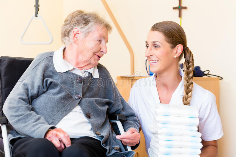 Nurse bringing supplies to woman in retirement home. Nurse bringing supplies to senior women in retirement home royalty free stock photo