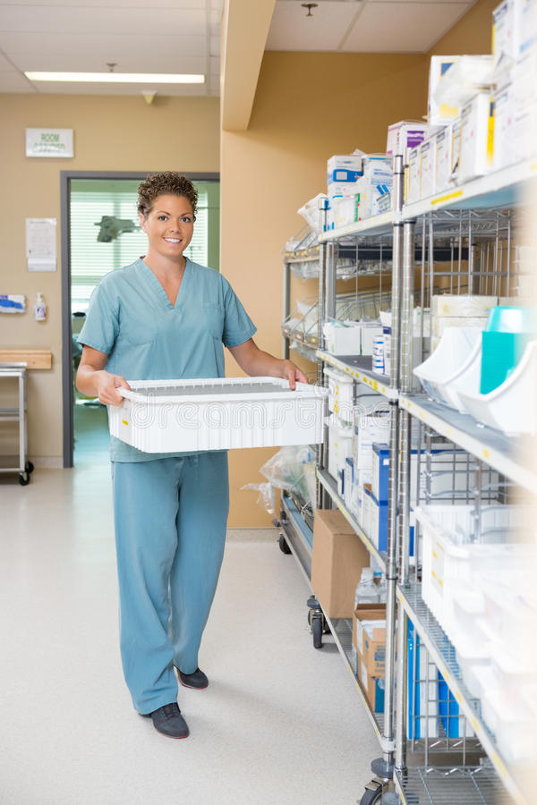 Nurse Carrying Container In Hospital Storage Room. Full length portrait of female nurse carrying container in hospital storage room royalty free stock image