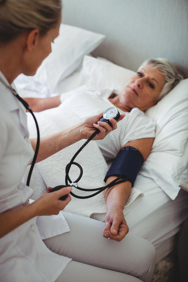 Nurse checking blood pressure of senior woman royalty free stock image